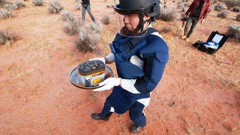 Ein Mitarbeiter der Japan Aerospace Exploration Agency (Jaxa) hält die kostbare Fracht in Händen