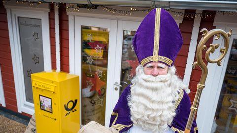 Ein Mann mit weißem Vollbart, violettem Bischofstab steht vor einem gelben Briefkasten