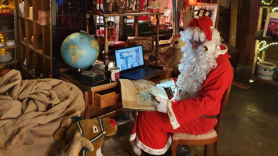 Ein Mann in einem Weihnachtsmann-Kostüm sitzt mit Smartphone und Tablet an einem kleinen Schreibtisch