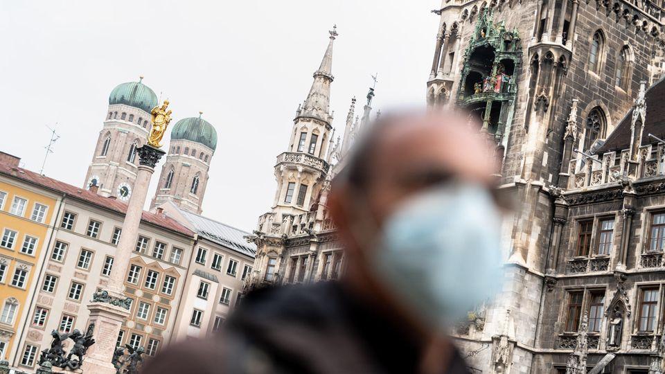 Bayern, München: Ein Mann mit Mundschutz geht über den Marienplatz