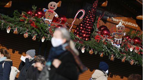 Coronavirus:  Passanten gehen an einem weihnachtlich geschmückten Stand in der Innenstadt vorbei