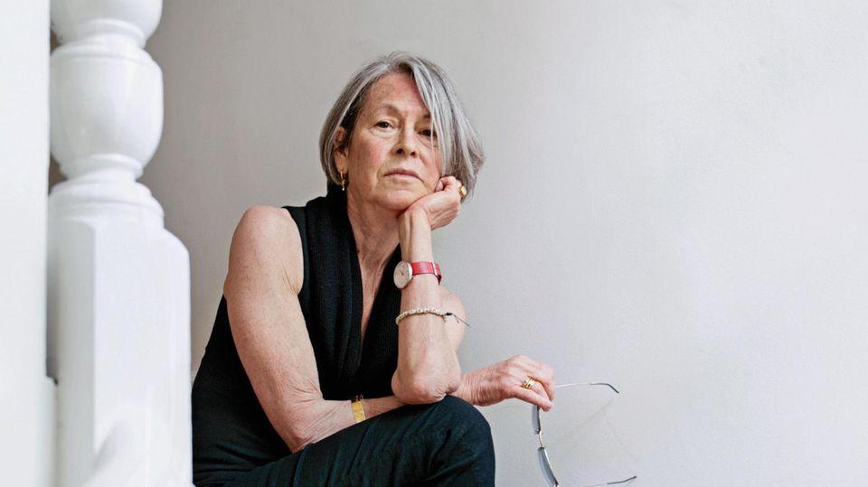 Literaturnobelpreisträgerin Louise Glück sitzt auf einer Treppe und schaut nachdenklich