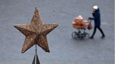 Der Stern eines überdimensionalen Adventskranzes ist vor dem fast leeren Domplatz in Erfurt zu sehen
