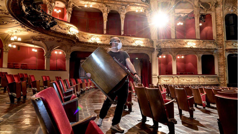 Ein Mitarbeiter trägt Stühle aus den Sitzreihen des Zuschauerraums des Berliner Ensembles