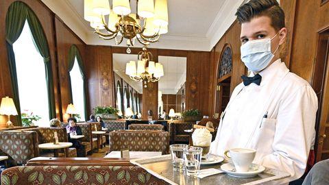 Ein klassisch gekleideter junger Kellner steht in einem Wiener Kaffeehaus. Auf seinem Tablett zwei Kaffeespezialitäten