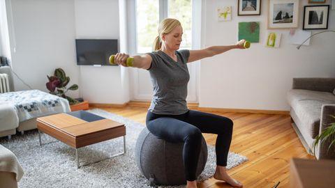 Frau macht Sport im Wohnzimmer mit Gymnastikball