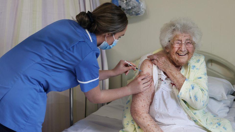 Ethel Jean Murdoch, eine 95-jährige Britin, sitzt auf ihrem Bett und erhält eine Corona-Impfung per Spritze