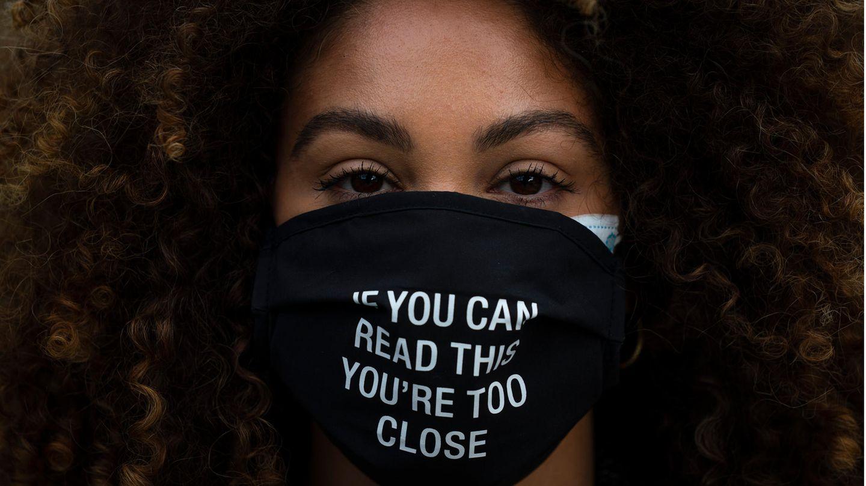 Frau trägt eine Schutzmaske mit der Aufschrift