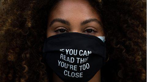 """Frau trägt eine Schutzmaske mit der Aufschrift """"If you can read this you're too close"""""""