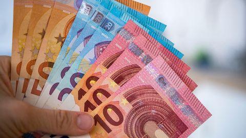 Kurzarbeit: Eine Frau hält Banknoten von 10, 20 und 50 Euro gefächert in der Hand