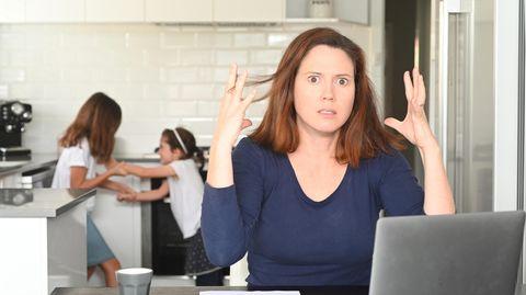 Eine Mutter am Rechner verzweifelt, weil im Hintergrund ihre Kinder streiten
