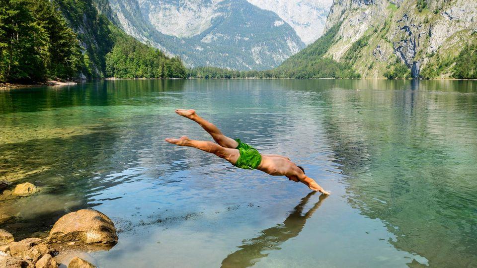 man springt mit Kopfsprung in den Obersee in Bayern