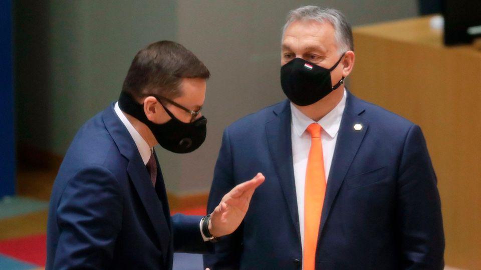 Polens MinisterpräsidentMateusz Morawiecki (l.) spricht während des EU-Gipfels in Brüssel mit dem ungarischen Regierungschef Viktor Orban