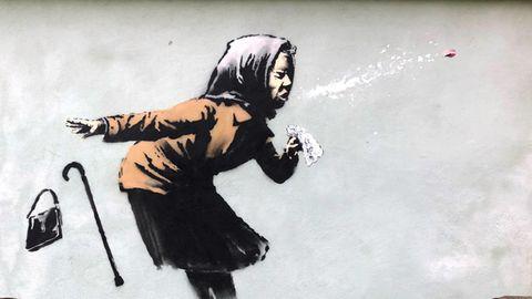 Auf einer hellgrünen Hauswand zeigt ein Graffito eine alte Frau mit Kopftuch, die beim Niesen ihr Gebiss verliert