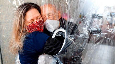 """Brasilien - """"Kuschelkontakt"""" und """"Umarmungs-Gardine"""" sind Worte, die es erst seit diesem Jahr gibt. Die Plastikfolie macht es möglich, dass Maria Paula Moraes ihren 82-jährigen Vater Wanderley im Juli das erste Mal nach 100 Tagen wieder spüren kann."""
