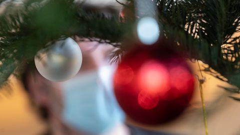 Ein Mann mit Mund-Nasen-Schutz hinter einem Weihnachtsbaum