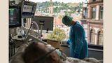 """Stuttgart, 14. Mai 2020 - Marienhospital  Musik hilft heilen: Die Gesundheits- und Krankenpflegerin Ivett Bodo (27) schaltet das Radio für einen Patienten an. Was dem Mann genau fehlt, ist unklar. Er zeigt zwar Covid-19-typische Symptome, Tests auf das Coronavirus fielen allerdings negativ aus. Die Musik soll seinen Genesungsprozess unterstützen.  """"Covid-19 hat uns täglich an Grenzen gebracht"""", sagt sie. """"Wir mussten mit den Möglichkeiten zurechtkommen, die wir hatten, mussten ausprobieren. Und aushalten, dass in manchen Fällen nichts mehr half."""""""