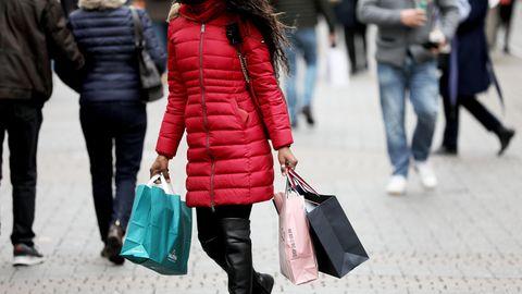 Nordrhein-Westfalen, Köln: Eine Frau geht mit Einkaufstaschen durch die Fußgängerzone