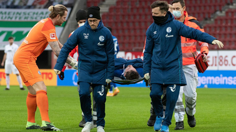 Schalkes Torwart Ralf Fährmann (l) beugt sich zu Mark Uth, der auf einer Trage verletzt vom Spielfeld getragen wird