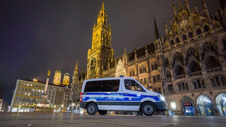 Ausgangssperre Bayern: Ein Polizeiwagen fährt über den menschenleeren Marienplatz