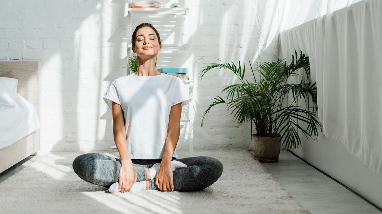 Frau sitzt in Wohnzimmer auf Teppich und meditiert