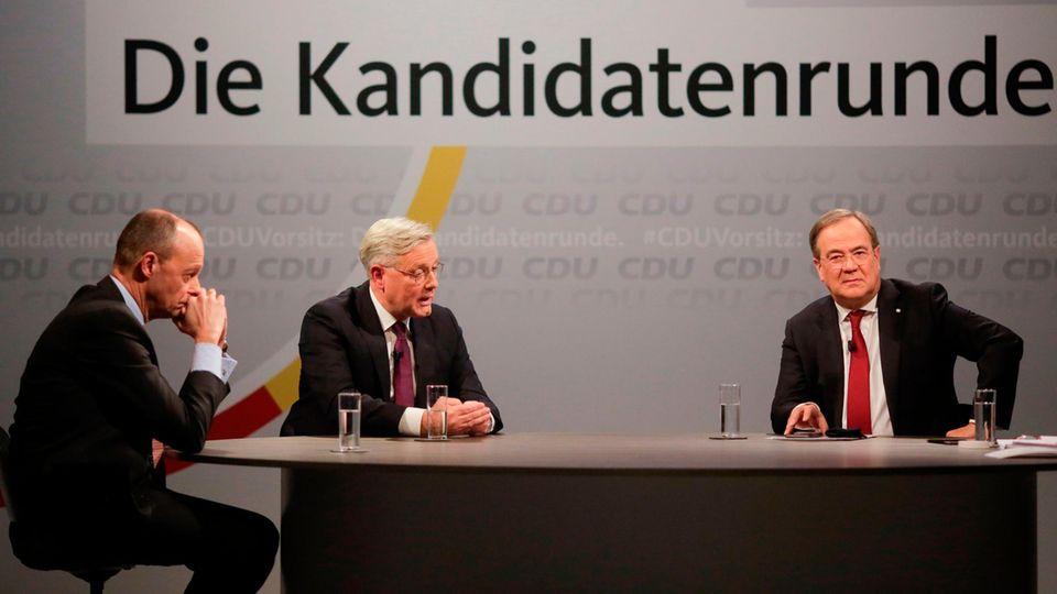 """Unter dem Schriftzug """"CDU-Vorsitz: Die Kandidatenrunde"""" sitzen drei Männer in Anzügen an einem ovalen Tisch"""