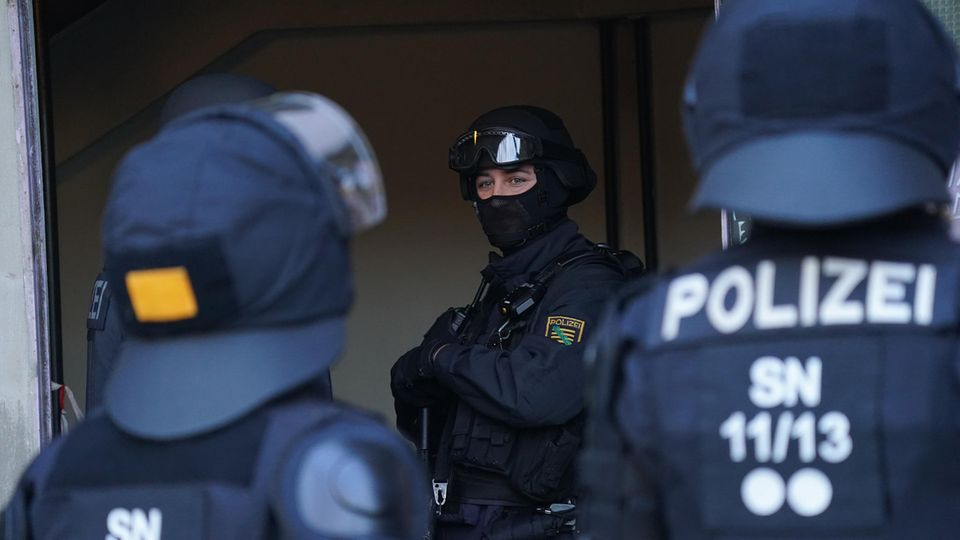 Drei schwer bewaffnete Polizisten in Schutzkleidung stehen im Eingangsbereich eines Gebäudes