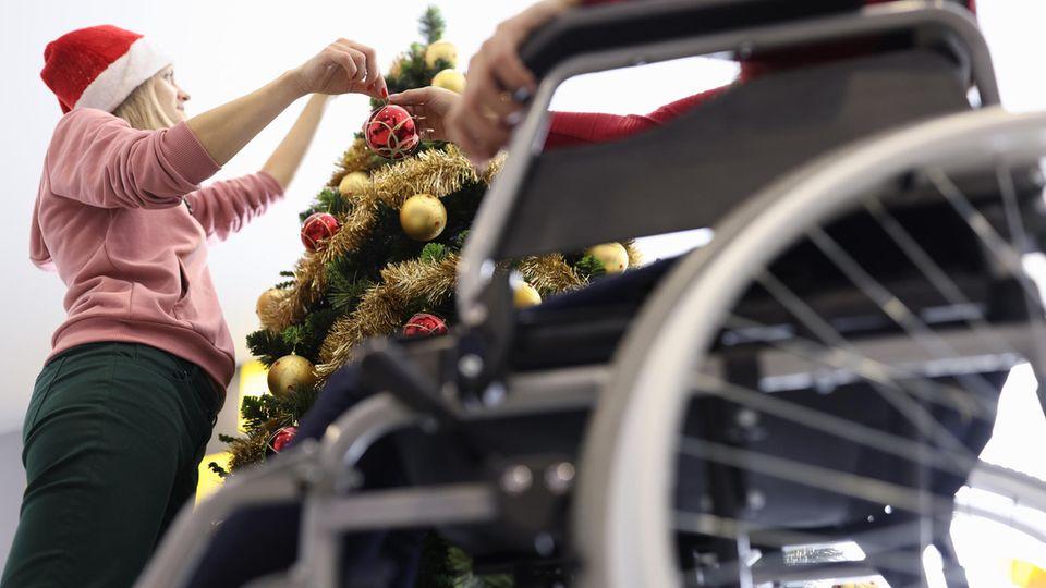 Ein Senior im Rollstuhl sitzt neben einem Weihnachtsbaum, den eine Pflegerin gerade schmückt