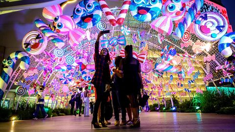 Bangkok: Selfie bei Weihnachts-Shopping  Am Eingang eines Einkaufzentrum machen diese jungen Thailänderinnen ein Foto mit der über ihnen strahlenden Fantasie-Deko.