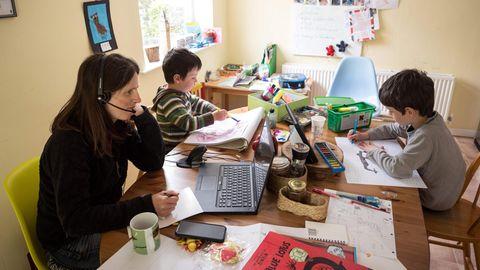 Eine Mutter arbeitet zuhause, während ihre beiden Kinder neben ihr für die Schule lernen