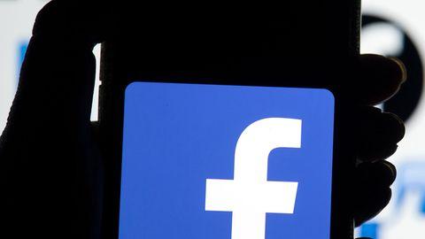 Eine linke Hand hält ein Smartphone, auf dessen Display das blau-weiße Logo von Facebook leuchtet