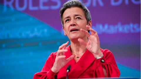 Eine Frau mit kurzen grauen Haaren steht in einer roten Bluse an einem blauen Rednerpult und gestikuliert mit beiden Händen