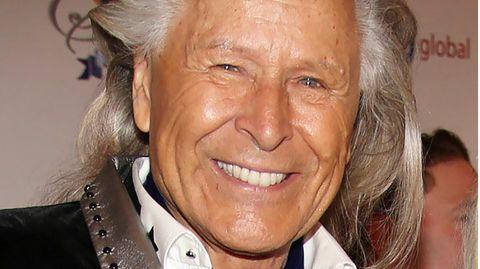 Ein Mann mit weiß-grauer, zurückgekämmter Mähne lächelt mit gebleckten Zähnen in die Kamera