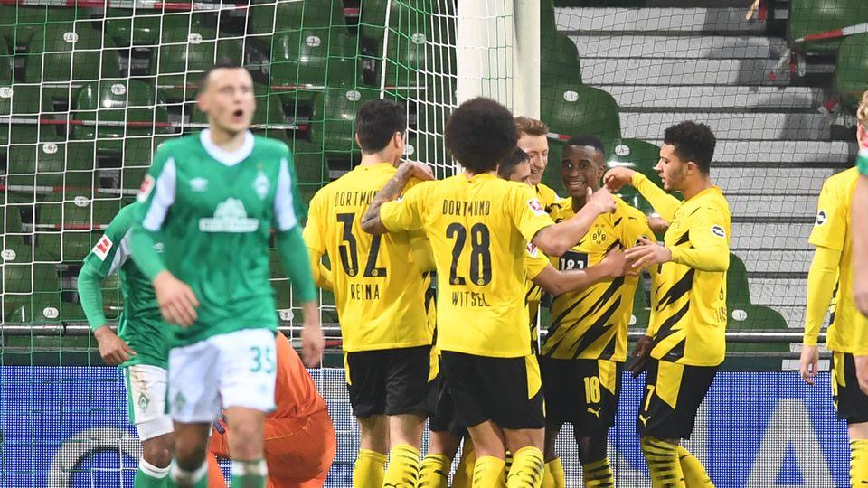 Die Spieler von Borussia Dortmund bejubeln in ihren schwarz-gelben Fußball-Trikots ein Tor