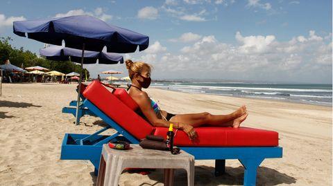 Eine Touristin auf Bali trägt beim Sonnen am Strand den obligatorischen Mund-Nasenschutz