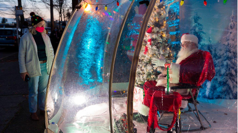 Bild 1 von 16der Fotostrecke zum Klicken: Social Distancing in Seattle  MitSicherheitsabstand in der Öffentlichkeit: Dieser Weihnachtsmann in Washington State plaudert mit einer Frau aus einer schützenden Plastikblase.