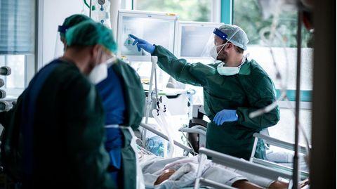 Mitarbeiter der Pflege in Schutzkleidung behandeln einen Patienten mit Corona-Infektion