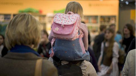 Ein Kind sitzt auf den Schultern seiner Mutter, die es durch ein sehr volles Geschäft trägt