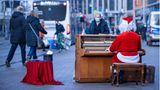 Schwerin: Weihnachtslieder in der Fußgängerzone  Kurz vor dem zweiten Lockdown: Ein als Weihnachtsmann verkleideter Straßenmusikant spielt in der Innenstadt auf seinem mobilen Klavier.