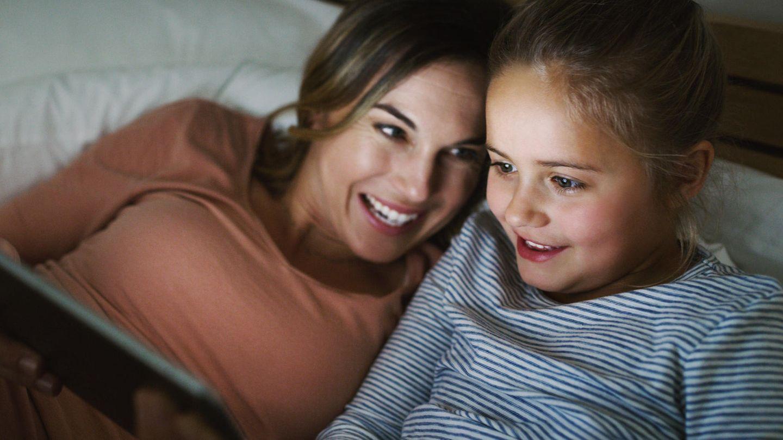 Mutter und Tochter liegen im Bett und schauen auf ein Tablet