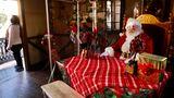 """Los Angeles: Mit Plexiglas geschützt  Ein als Weihnachtsmann verkleideter Mann sitzt aufgrund der Ansteckungsgefahr mit dem Coronavirus hinter Plexiglaswänden in einem Raum inden """"Citadel Outlets""""."""