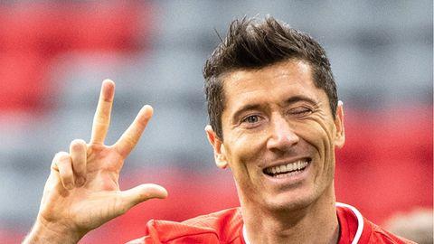 Bayern-Spieler Robert Lewandowski zeigt beim Torjubel eine Drei mit den Fingern und kneift ein Auge zu