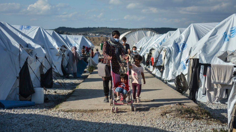Eine Familie läuft im Camp Kara Tepe zwischen den Zelten