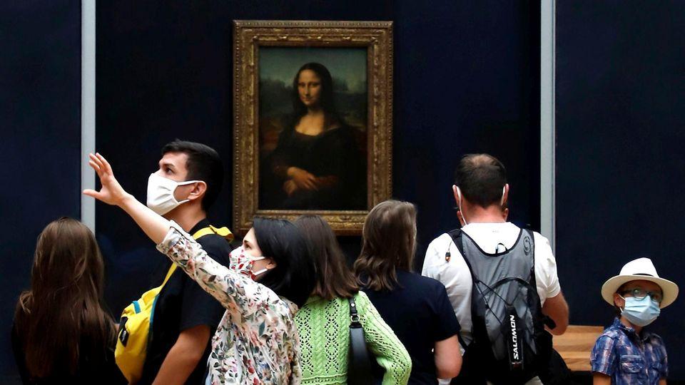 """Besucher tragen Mundschutze während sie im Museum Louvre Leonardo da Vincis Meisterwerk """"Mona Lisa"""" betrachten"""