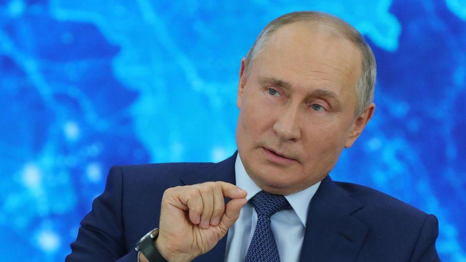 Vor einer blau beleuchteten Weltkarte sitzt Russlands Präsident Wladimir Putin im Anzug und gestikuliert mit der rechten Hand