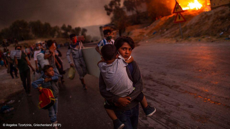 """Lesbos, Griechenland:Am 9. September 2020 zerstört im Flüchtlingslager Moria auf der griechischen Insel Lesbos ein Feuer die Unterkünfte von 13.000 Menschen, darunter 4.000 Kinder. Sie sind von Krieg und Gewalt geflohen. Sie haben unter elenden Bedingungen ausgeharrt, viele seit Jahren. Das Lager ist überfüllt, Krankheiten grassieren, immer wieder werden Lebensmittel und sauberes Wasser knapp. Und nun das Feuer. Es breitet sich rasend schnell aus, den Flüchtlingen bleibt nur, in die Hand zu nehmen, was sie greifen können. Unter den vielen Bildern von dieser Inferno-Nacht hat der griechische Fotograf Angelos Tzortzinis die eindrucksvollsten vom Leiden der Kinder gemacht. Und jenes Foto, das alles gleichzeitig zeigt: Flucht und Tapferkeit, Fassungslosigkeit und Hilfsbereitschaft in höchster Not. Die Stärke des Kleinen, der dem noch Kleineren die heile Haut bewahrt. Unter den nach UNO-Schätzungen gegenwärtig rund 79,5 Millionen Menschen auf der Flucht sind etwa 32 Millionen Kinder und Jugendliche.  Angelos Tzortzinis, geboren in Athen, hat an der Leica Academy of Creative Photography studiert und seither überwiegend als freier Fotograf gearbeitet. Er hat aus Georgien berichtet und vom Erdbeben in Haiti 2010, vom """"Arabischen Frühling"""" in Kairo und dem Krieg in Libyen. Vor allem aber beschäftigt ihn die Situation der Flüchtlinge in seinem Heimatland."""