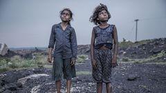 """Indien:Die Kohlefelder von Jharia im Bundesstaat Jharkhand gehören zu den größten in ganz Asien. Auf 280 Quadratkilometern wird hier Kohle im Tagebau gewonnen. Es ist das Land der schwarzen Gesichter. Giftiges Land, denn seit über 100 Jahren steigen hier aus ungezählten unterirdischen Feuern toxische Gase auf: Schwefeldioxid, Kohlenmonoxid. Luft und Trinkwasser sind verschmutzt, Asthma, Tuberkulose und Hautkrankheiten grassieren. Trotzdem halten es Menschen hier aus, ziehen sogar auf der Suche nach Arbeit hierher. Und auch Kinder arbeiten in den offenen Minen, schleppen Steine. Der indische Fotograf Supratim Bhattacharjee hat in den Gesichtern dieser Kinder ihr ganzes Elend eingefangen, Entsetzen, Erschöpfung, Zerstörung. Die Eltern sind meist Analphabeten. Der Tageslohn, umgerechnet ein bis zwei US-Dollar, in den oft illegal betriebenen Minen am Rande der großen Kohlefelder ist derart gering, dass schon Vier-, Fünf-, Sechsjährige zur Mitarbeit gezwungen sind. Viele Mädchen und Jungen sind mangelernährt; zur Schule gehen sie nicht.  Supratim Bhattacharjee wurde 1983 in Boraipur bei Kalkutta geboren und hat für Filmproduktionen gearbeitet, bevor er Fotograf wurde. Umwelt- und Menschenrechtsthemen stehen in seinem Fokus, vor allem aber beschäftigt ihn die sozio-ökonomische Situation in seinem Heimatland. Die Kinder von Jharia zu erleben, schreibt Bhattacharjee, hätte ihn nicht nur geschmerzt. Sie seien """"ein Schock"""" für ihn gewesen."""