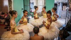 """Brasilien:Gewalt und Drogen kennenzulernen, früh schwanger zu werden – das gehört zu den Alltagserfahrungen von Kindern und Jugendlichen in den Favelas von Rio de Janeiro. Eine Gruppe von Mitgliedern einiger der besten Tanz-Akademien Brasiliens aber hat beschlossen, für eine Alternative zu sorgen: In der Favela Manguinhos haben sie eine Ballettschule eröffnet. 250 Mädchen und junge Frauen soll sie den Weg aus der täglichen Misere zeigen. Durch Freude und Spiel, durch Disziplin und ein neues Selbstbewusstsein. Eine Bibliothek gehört zur Schule – und viermal im Monat ein Ausflug in das imposante Teatro Municipal, wo den Mädchen eine persönliche Begegnung mit ihren Idolen geboten wird. Der Fotograf Evgeny Makarov hat die Ballettschülerinnen von Manguinhos auf ihren Wegen durch die Favela begleitet, beim Training in der Schule, die er als einen """"Schutzbunker""""beschreibt, beim Training zuhause, wo sie in armseliger Umgebung """"Arabesque"""" und """"Grand Plié"""" üben – und in einer Gemeinschaft, die sie glücklich macht.  Evgeny Makarov, 1984 in St. Petersburg geboren, kam mit seiner Familie 1992 nach Deutschland. Dort studierte er Politikwissenschaft an der Universität Hamburg und entdeckte die Fotografie als Medium, """"soziale Realität direkter zu erfassen als mit einem akademischen Zugang"""".Gegenwärtig lebt Makarov in Brasilien."""