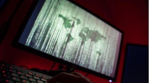 Ein Mann sitzt am Rechner und tippt auf einer Tastatur