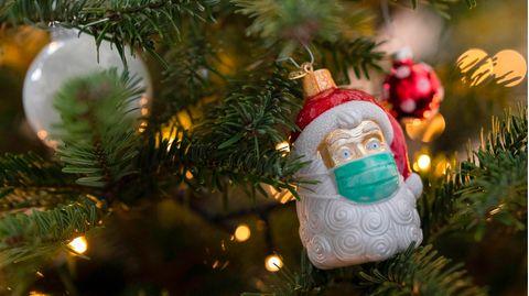 An einem Weihnachtsbaum hängt Weihnachtsschmuck in Form eines Weihnachtsmannes, der eine Maske trägt